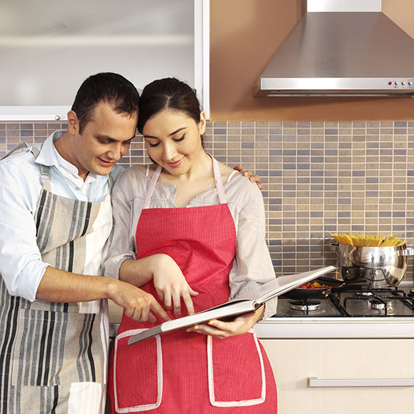 Young couple reading cook book in kitchen.