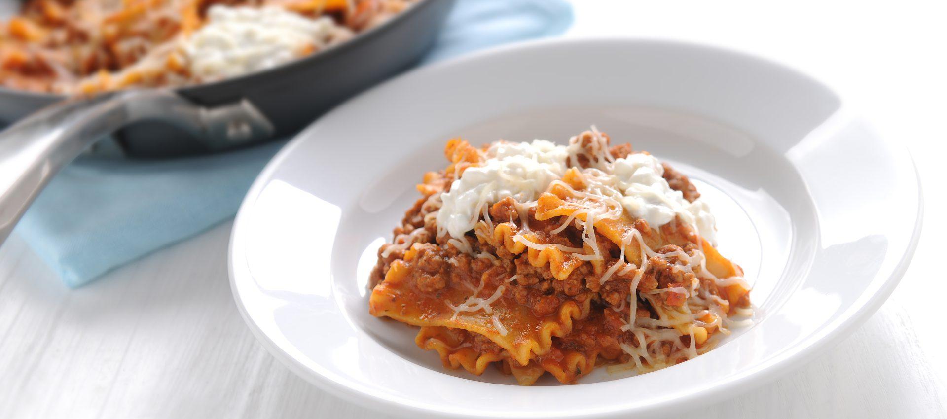 Italian skillet lasagna with ground beef, pasta sauce, ricotta, and Italian shredded cheese