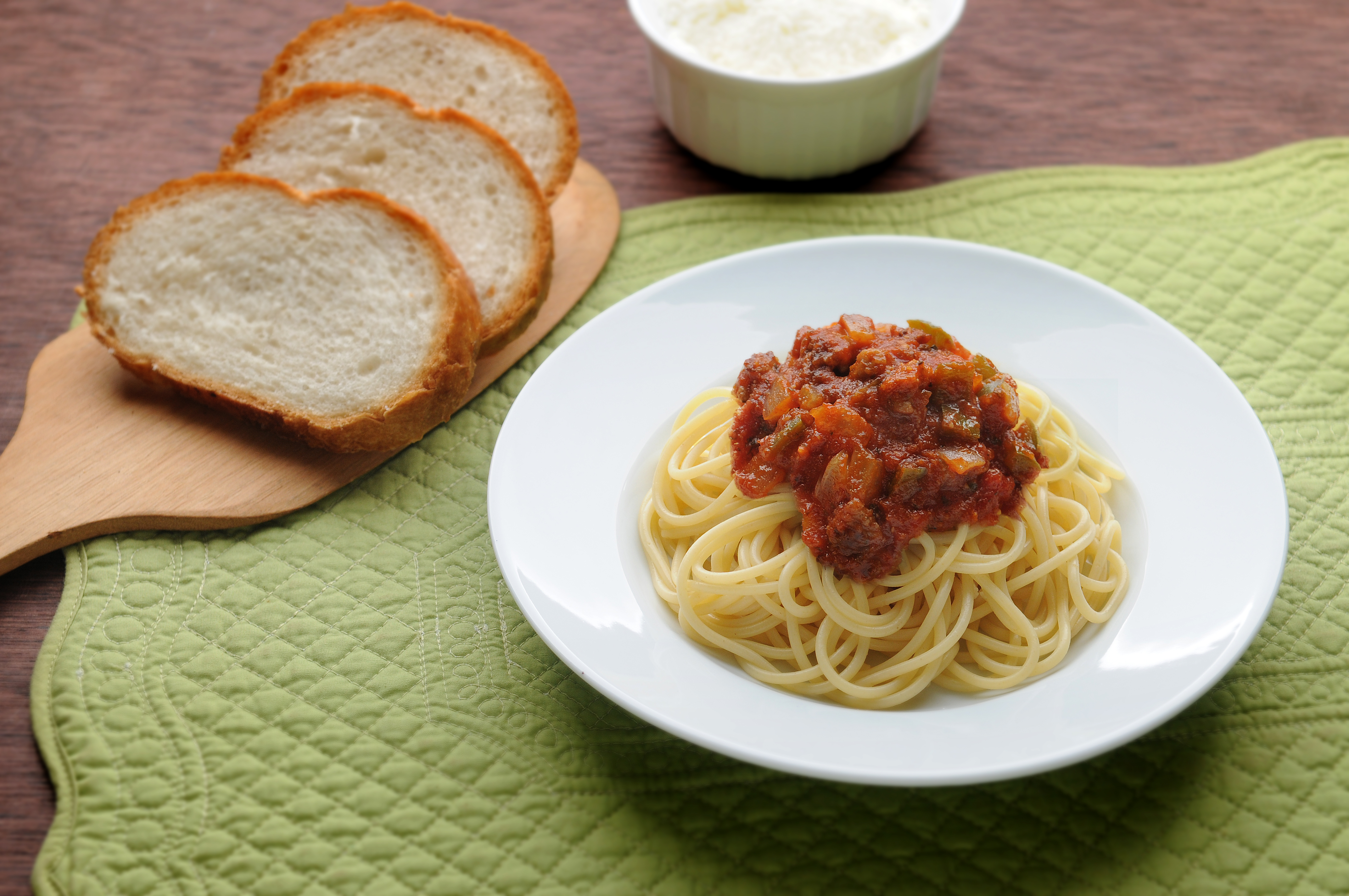 Spaghetti with Italian red sauce with onions and bell peppers and a side of bread